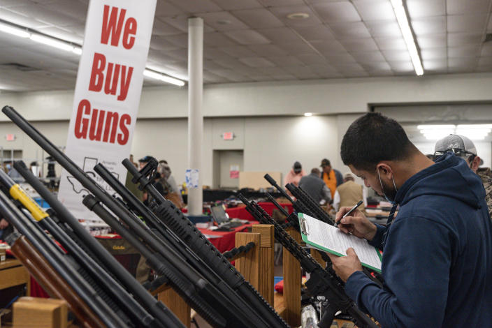 FILE - Ivan Gonzalez fills out paperwork while purchasing a gun at the Silver Spur Gun and Blade Show, Saturday, Jan. 23, 2021, in Odessa, Texas. After a year of pandemic lockdowns, mass shootings are back, but the guns never went away. As the U.S. inches toward a post-pandemic future, guns are arguably more present in the American psyche and more deeply embedded in American discourse than ever before. The past year's anxiety and loss fueled a rise in gun ownership across political and socio-economic lines. (Eli Hartman/Odessa American via AP, File)