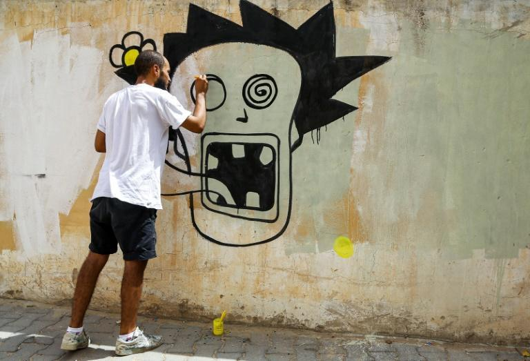 Graffiti artist Kaisser Grojja, also known as 'Wolf Gang', works on a mural in Sidi Bouzid in central Tunisia (AFP/ANIS MILI)