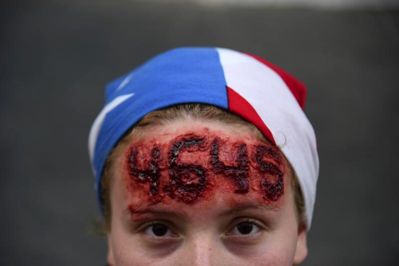 Nicole Diaz wears special effects make-up with hurricane Maria's death toll number written on her forehead, while protesting against Governor Ricardo Rossello, in San Juan, Puerto Rico, Friday, July 19, 2019. Protesters are demanding Rossello step down for his involvement in a private chat in which he used profanities to describe an ex-New York City councilwoman and a federal control board overseeing the island's finance. (AP Photo/Carlos Giusti)