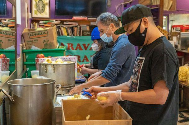 PHOTO: Volunteers J.J. Kingsman, front, Leo Alexandropoulos, middle, with Yajaira Saavedra, Mutual Aid Coordinator for La Morada, preparing applesauce that will feed about 450 people. (ABC News)