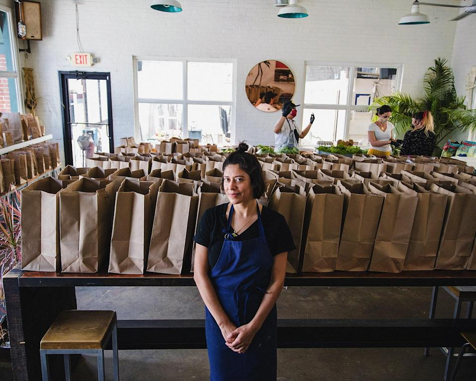 """<div class=""""caption""""> Maricela Vega stands among CSA bags being prepared for customer pickup in the dining room of 8Arm. </div> <cite class=""""credit"""">Photo By DUSTIN CHAMBERS</cite>"""