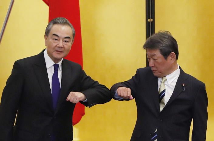 China' Foreign Minister Wang Yi, left, and his Japanese counterpart Toshimitsu Motegi bump elbows at the start of their talks amid the coronavirus outbreak, in Tokyo on Tuesday, Nov. 24, 2020. Wang met Motegi on Tuesday to discuss ways to revive their pandemic-hit economies as well as regional concerns over China's growing influence. (Issei Kato/Pool Photo via AP)