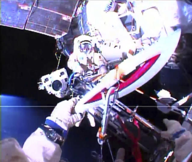 Russian astronaut Oleg Kotov holds an Olympic torch as he takes it on a spacewalk as Russian astronaut Sergei Ryazansky prepares the camera outside the International Space Station in this still image taken from video courtesy of NASA TV, November 9, 2013. A pair of Russian cosmonauts took the Olympic torch into open space for the first time in history on Saturday as part of the torch relay of the Sochi 2014 Winter Games. REUTERS/NASA TV/Handout via Reuters (OUTER SPACE - Tags: ENVIRONMENT SCIENCE TECHNOLOGY SPORT OLYMPICS) ATTENTION EDITORS - THIS IMAGE WAS PROVIDED BY A THIRD PARTY. FOR EDITORIAL USE ONLY. NOT FOR SALE FOR MARKETING OR ADVERTISING CAMPAIGNS. THIS PICTURE IS DISTRIBUTED EXACTLY AS RECEIVED BY REUTERS, AS A SERVICE TO CLIENTS
