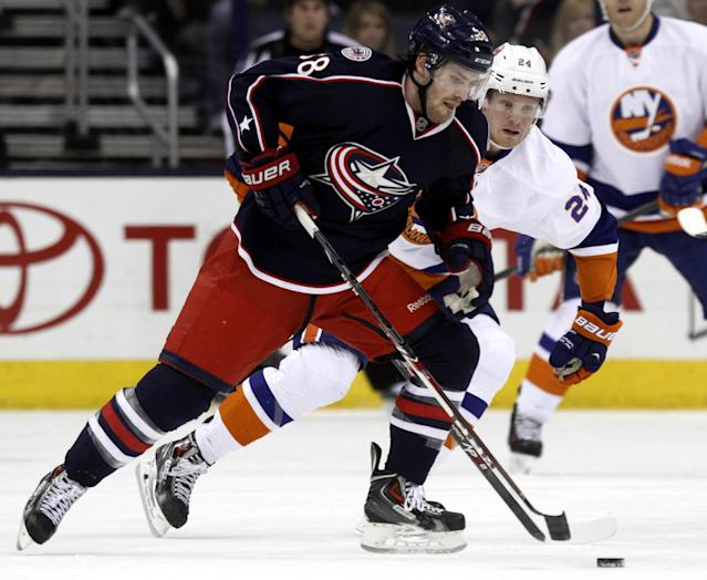 Columbus Blue Jackets' Boone Jenner, left, works for the puck against New York Islanders' Kevin Czuczman in the first period of an NHL hockey game in Columbus, Ohio, Sunday, April 6, 2014. (AP Photo/Paul Vernon)