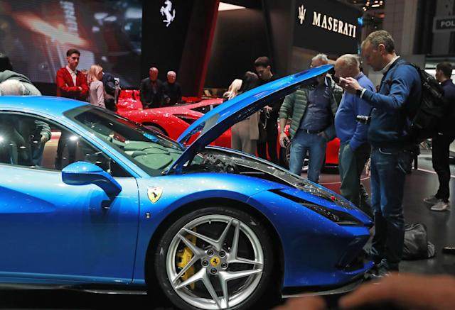 People at the Ferrari stand at the Geneva International Motor Show in Switzerland, on 7 March 2019. (Sergei Fadeichev\TASS via Getty Images)