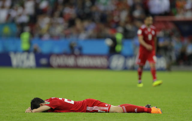 Iran's Sardar Azmoun lies flat out in the ground after the end of the group B match between Iran and Spain at the 2018 soccer World Cup in the Kazan Arena in Kazan, Russia, Wednesday, June 20, 2018. Spain won the game 1-0. (AP Photo/Sergei Grits)
