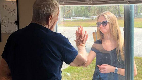 PHOTO: Carly Boyd announces her engagement to her grandfather Shelton Mahala, 87, through his nursing home window in Lake Waccamaw, N.C., in a photo shared on Facebook March 16, 2020. (Courtesy Premier Living & Rehab Center)
