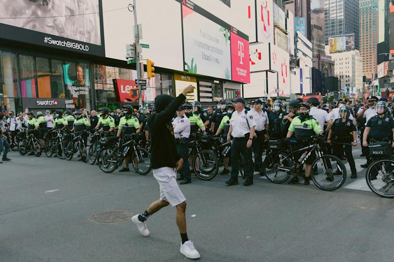 A protester walks by officers in Times Square on May 30. | Mark Clennon