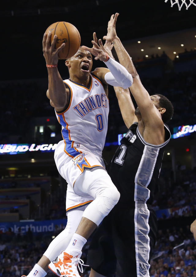 Oklahoma City Thunder guard Russell Westbrook (0) goes up to shoot as San Antonio Spurs forward Tim Duncan defends during the first quarter of an NBA basketball game in Oklahoma City, Thursday, April 3, 2014. (AP Photo/Sue Ogrocki)