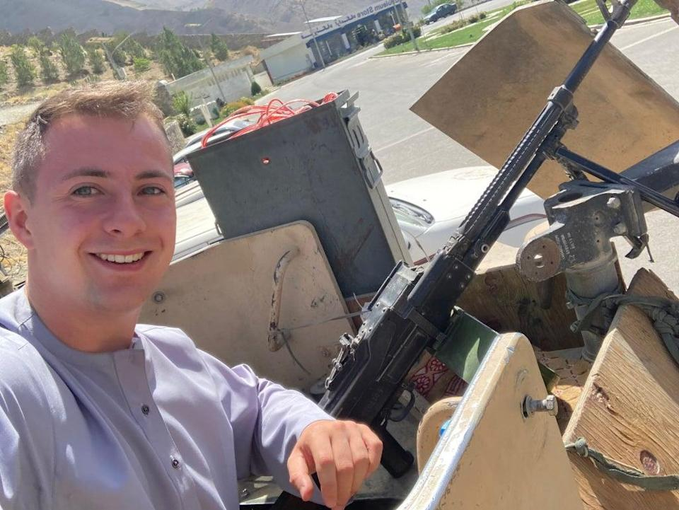 Miles Routledge poses with what is believed to be an Afghan military gun after meeting the soon-to-be defeated army during his visit (Miles Routledge/PA)