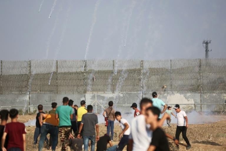 Palestinian protesters in Gaza watch incoming tear gas canisters shot by Israeli security forces amid clashes near the border fence on Saturday