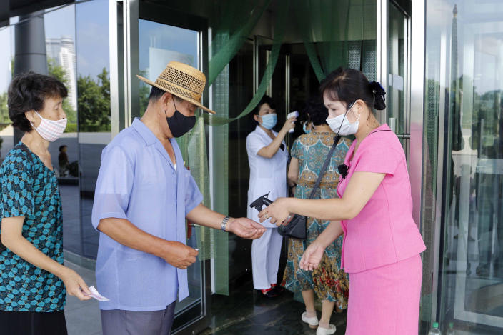 Two employees get a temperature check in Pyongyang, North Korea. (AP)