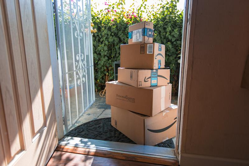 Image of an Amazon packages. Amazon is an online company and is the largest retailer in the world. Cardboard package delivery at front door during the holiday season. shipping package parcel box on wooden floor with protection paper inside. Amazon.com went online in 1995 and is now the largest online retailer in the world.