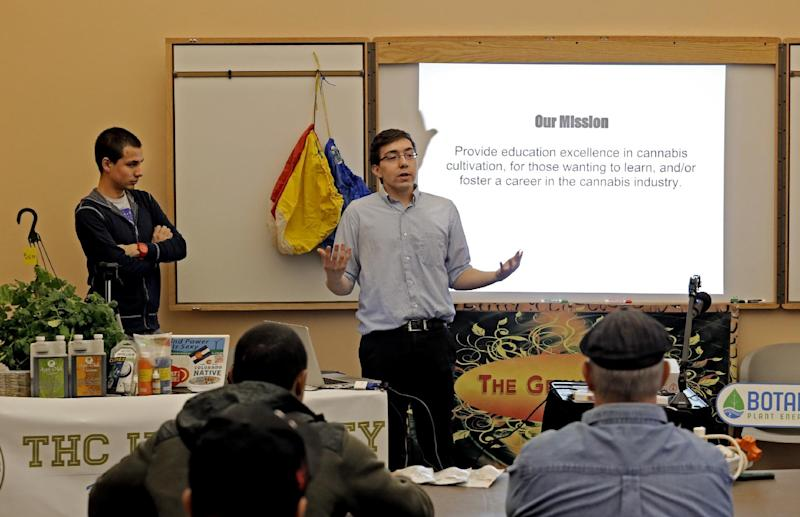 """In this photo taken on Saturday, Feb. 9, 2013, THC University co-founder Matt Jones, center, speaks to the first class as co-founder Freeman LaFleur, left, looks on at THC University that was held at the Tivoli in Denver. Watery failure is what inspired the """"Marijuana 101"""" class, which was organized by Matt Jones, a 24-year-old Web developer who wanted to get in the marijuana business without raising or selling it himself. (AP Photo/Ed Andrieski)"""