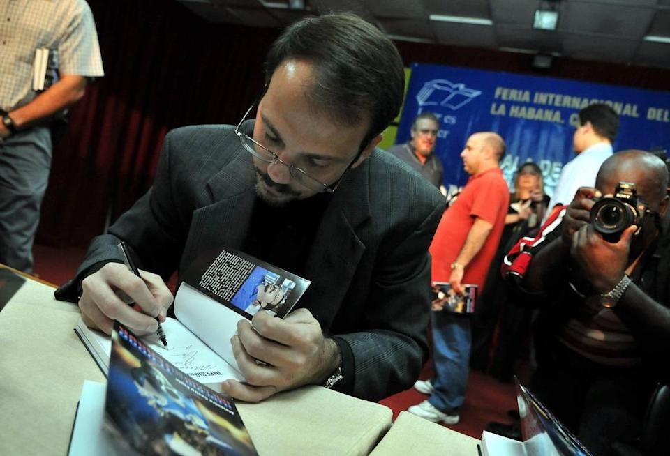 "Col. Alejandro Castro Espín, son of Raúl Castro and nephew of Fidel Castro, signs a copy of his book ""Imperio del Terror,"" on Feb. 21, 2009 during the Havana's International Book Festival in Cuba. EFE/Alejandro Ernesto"