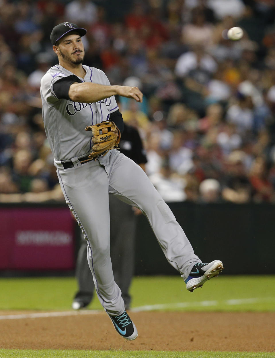 Colorado Rockies third baseman Nolan Arenado makes the off-balance throw for the out on a ball hit by Arizona Diamondbacks' Paul Goldschmidt in the fourth inning during a baseball game, Friday, Sept. 21, 2018, in Phoenix. (AP Photo/Rick Scuteri)