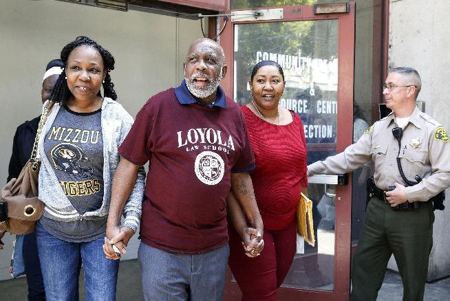 Andrew Wilson, center, is accompanied by his daughters, Catrina Burks, left, and Gwen Wilson, second from right, as he leaves the Men's Central Jail in Los Angeles, Thursday, March 16, 2017. Wilson, whose murder conviction was tossed by a California judge is free after 32 years in prison. (AP Photo/Nick Ut)