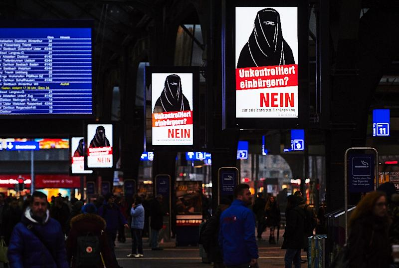 """People walk past electoral posters by the Committee Against Facilitated Naturalization/Citizenship reading """"Uncontrolled Naturalisation? No"""" with the illustration of a woman wearing a niqab, in a train station in Zurich, on February 7, 2017 (AFP Photo/Michael BUHOLZER)"""