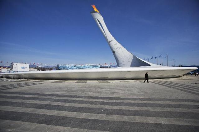 A man walks behind the Olympic cauldron before the closing ceremony of the 2014 Winter Olympics, Sunday, Feb. 23, 2014, in Sochi, Russia. (AP Photo/Pavel Golovkin)