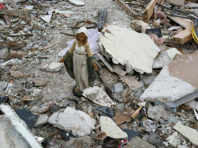 In a November 2013 family photo provided by Annmarie Klein, a statue of the Blessed Virgin Mary stands amid the ruins of the former home of Klein and her family in Washington, Ill., after the Nov. 17, 2013 that destroyed their home. Klein is asking for the public's help in locating three cards swept away by the twister. The cards were addressed to the three children of Klein's brother, Paul McLaughlin, who before his 2005 death from colon cancer entrusted Klein to give the cards to his children someday. (AP Photo/Kara Kamienski via Annmarie Klein)
