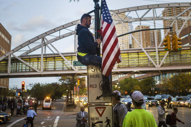 <p>A man places a U.S. flag in memory of the victims of the recent truck attack on the bike path near the crime scene Thursday, Nov. 2, 2017, in New York. (Photo: Andres Kudacki/AP) </p>