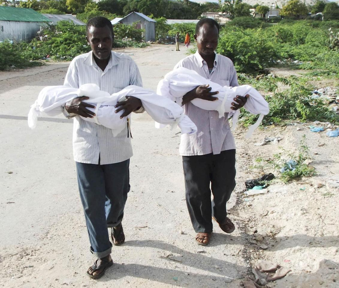 Hassan Abdulkadir Adan, left, and Moktar Hassan Garad, right, from southern Somalia carry their dead 7 and 5 year-old boys from a local hospital in Mogadishu, for burial Tuesday, Aug. 16, 2011, The World Food Program said Saturday that it is expanding food distribution efforts in famine-ravaged Somalia, where the U.N. has estimated that only 20 percent of people needing aid are able to receive it because an al-Qaida-linked group controls large portions of the country. (AP Photo/Farah Abdi Warsameh)