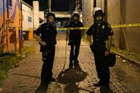 Police officers stand in a taped-off area where a police officer was shot as protesters marched in Louisville, Kentucky