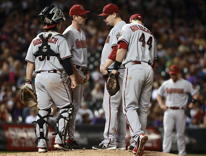 Arizona Diamondbacks starting pitcher Trevor Cahill, third from left, confers with catcher Tuffy Gosewisch, left, pitching coach Charles Nagy, second from left, and first baseman Paul Goldschmidt after Cahill gave up two singles to the Colorado Rockies in the sixth inning of a baseball game in Denver on Saturday, Sept. 21, 2013. (AP Photo/David Zalubowski)