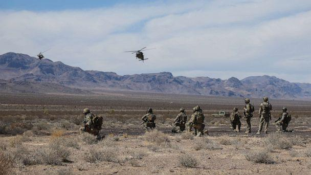 PHOTO: U.S. Special Forces Soldiers and Airmen from the 99th Civil Engineer Squadron EOD team and 66th Rescue Squadron, watch as two UH-60 Blackhawk helicopters land at the Nevada Test and Training Range near Nellis AFB, Nevada, Aug. 28, 2018. (Sgt. Connor Mendez/U.S. Army )