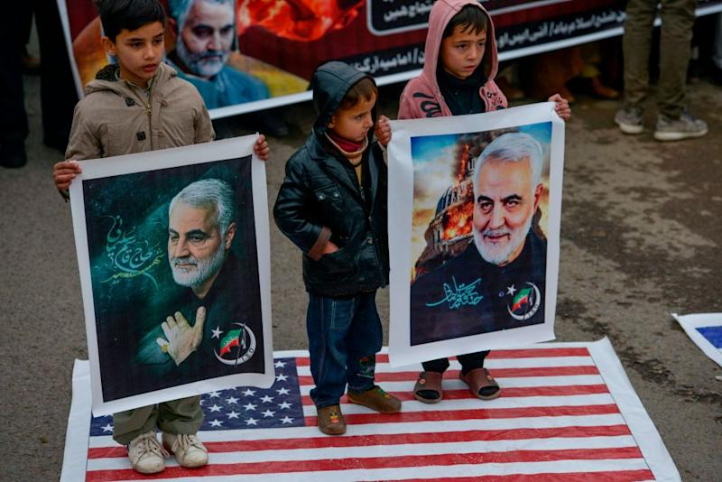 Shiite Muslim children stand on the US flag as they hold pictures of Iranian commander Qasem Soleimani during a protest Sunday. Source: Getty