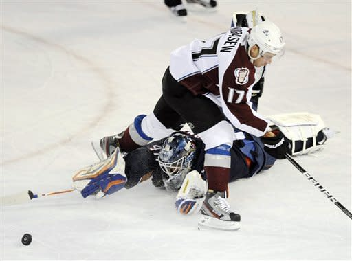 Edmonton Oilers' goalie Devan Dubnyk, bottom, intercepts the puck from Colorado Avalanche Chuck Kobasew during the first period of an NHL hockey game, Tuesday, Jan. 31, 2012, in Edmonton, Alberta. (AP Photo/The Canadian Press, John Ulan)