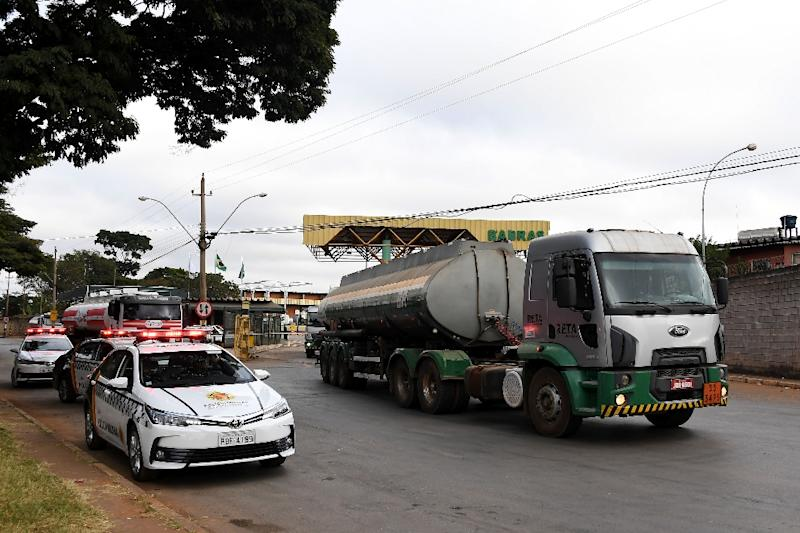A fuel truck leaves a distribution plant escorted by police in Brasilia on May 28, 2018 (AFP Photo/EVARISTO SA)