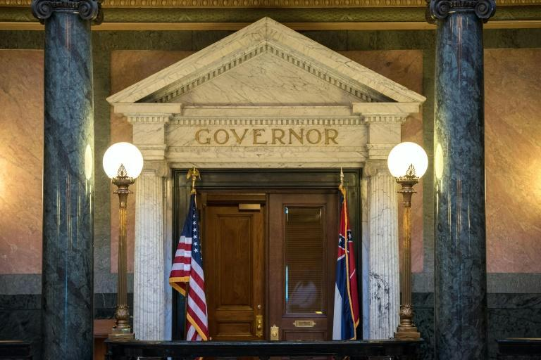 The Mississippi state flag (R) is seen outside the governor's office at the state capitol building in Jackson, Mississippi -- Governor Tate Reeves has said he will sign the bill to change the flag into law (AFP Photo/Rory Doyle)