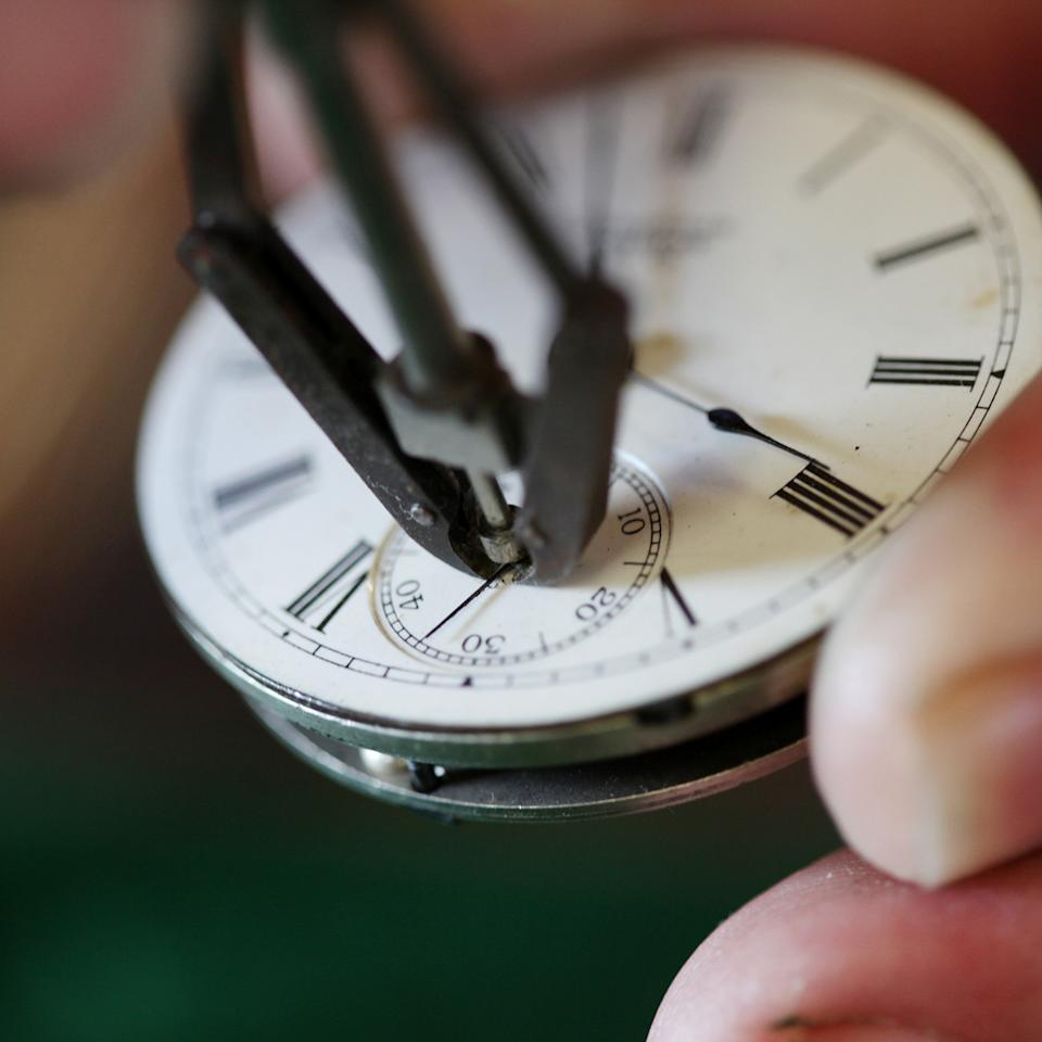 Mike Conroy - owner of Ye Old Watch shop in Portsmouth, Va. removes the second hand from an antique pocket watch.