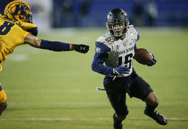 Utah State wide receiver Jordan Nathan (16) carries the ball as Kent State safety Elvis Hines (8) defends during the first half of the Frisco Bowl NCAA college football game Friday, Dec. 20, 2019, in Frisco, Texas. (AP Photo/Brandon Wade)