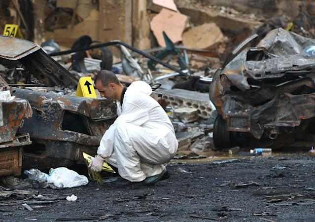 A Lebanese Army investigator inspects the site of a car bomb explosion in an overwhelmingly Shiite area and stronghold of the Lebanese militant group Hezbollah, in a southern suburb of Beirut, Lebanon, Friday, Aug. 16, 2013. A powerful car bomb tore through a bustling south Beirut neighborhood that is a stronghold of Hezbollah on Thursday, killing tens of people and trapping dozens of others in an inferno of burning cars and buildings in the bloodiest attack yet on Lebanese civilians linked to Syria's civil war. (AP Photo/Hussein Malla)