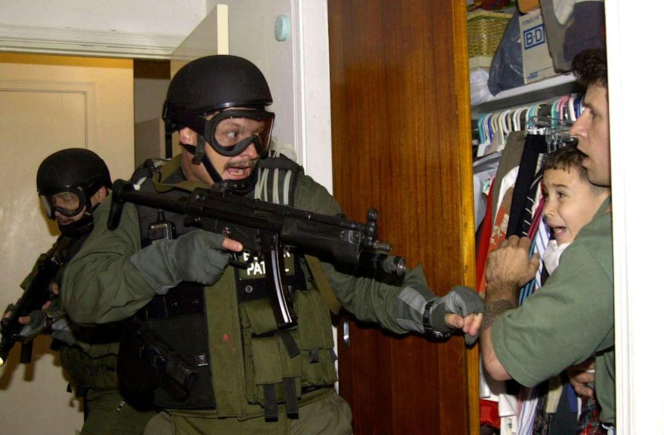 <p>2000. AP Caption: Elian Gonzalez is held in a closet by Donato Dalrymple, one of the two men who rescued the boy from the ocean, right, as government officials search the home of Lazaro Gonzalez for the young boy in Miami. U.S.-based relatives fought to keep Gonzalez, rescued at sea at age 5 after his mother died, but U.S. officials finally sent him back to his father in Cuba.</p>