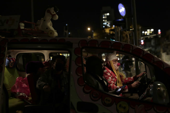 Protesters sit in a car as they gather under a bridge on their way to Israeli Prime Minister Benjamin Netanyahu's official residence in Jerusalem, Saturday, Jan. 30, 2021. (AP Photo/Maya Alleruzzo)