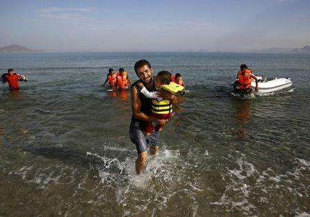 An Iranian migrant cries as while carrying his son after a small group of exhausted migrants from Iran arrived by paddling an engineless dinghy from the Turkish coast (seen in the background) at a beach on the Greek island of Kos August 15, 2015. REUTERS/Yannis Behrakis