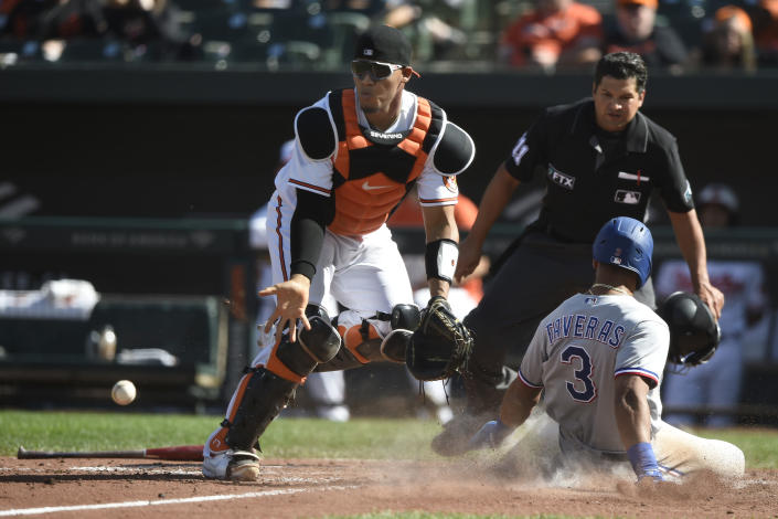 Texas Rangers' Jose Trevino is safe at the plate on a double by Isiah Kiner-Falefa, as Baltimore Orioles catcher Pedro Severino awaits the throw in the seventh inning of a baseball game. Sunday, Sept. 26, 2021, in Baltimore. (AP Photo/Gail Burton)