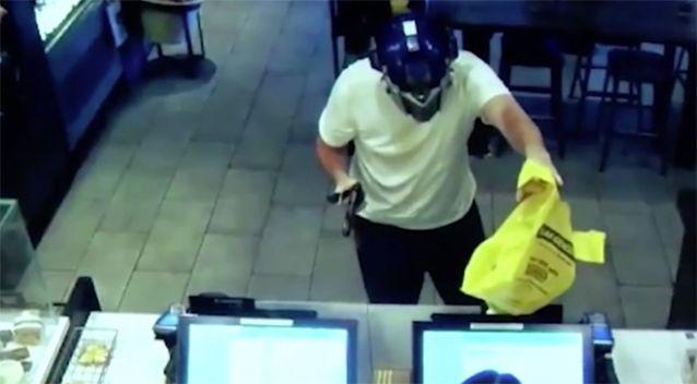 The alleged thief approaches the counter wielding a knife and gun-shaped item. Source: Fresno Police