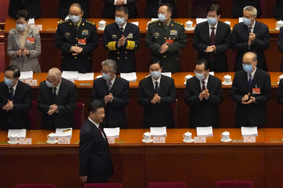 Delegates applaud as Chinese President Xi Jinping arrives for the opening session of China's National People's Congress (NPC) at the Great Hall of the People in Beijing, Friday, March 5, 2021. (AP Photo/Andy Wong)