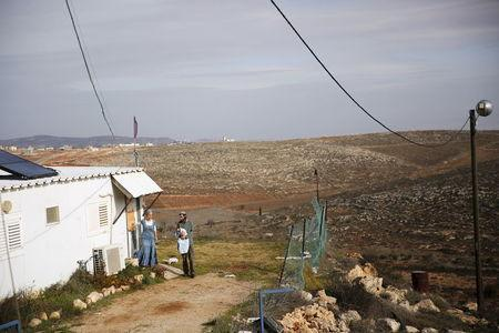Jewish settler Refael Morris stands with his wife and baby near their house in the unauthorised Jewish settler outpost of Achiya, south of the West Bank city of Nablus January 5, 2016. REUTERS/Ronen Zvulun