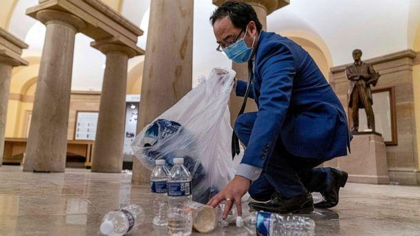 PHOTO: Rep. Andy Kim, Democrat from New Jersey, cleans up debris and trash strewn across the floor in the early morning hours, Jan. 7, 2021, after protesters stormed the Capitol in Washington, D.C., the day before. (Andrew Harnik/AP)