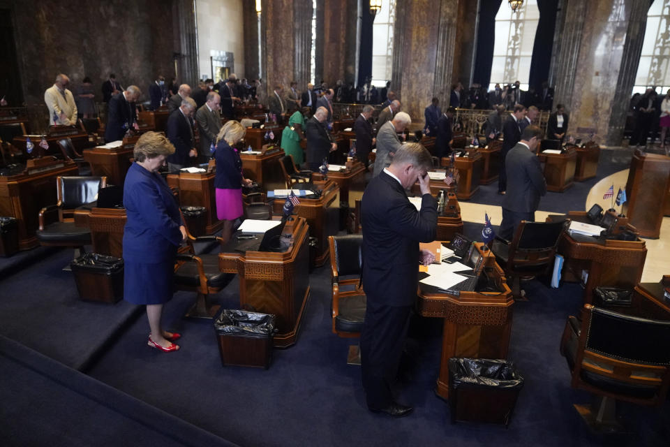 Lawmakers bow their heads in prayer during the invocation at the start of a veto session in the Senate Chambers in Baton Rouge, La., Tuesday, July 20, 2021. Louisiana state senators have narrowly voted to overturn Democratic Gov. John Bel Edwards' rejection of a bill prohibiting transgender students from participating in school sports. The vote came Tuesday on the opening day of the first veto session under the state's nearly 50-year-old constitution. (AP Photo/Gerald Herbert)