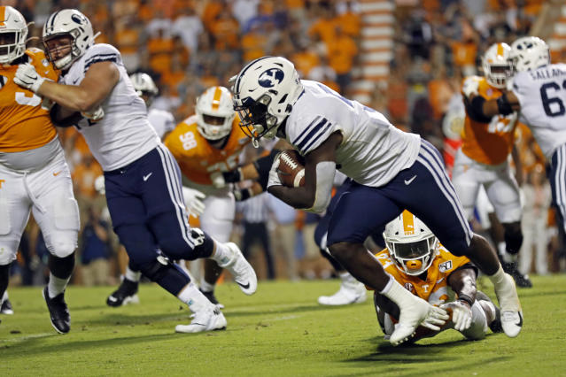 Brigham Young running back Ty'Son Williams (5) escapes the grasp of Tennessee linebacker Will Ignont (23) to score a touchdown on a 5-yard run to give his team a 29-26 win in overtime an NCAA college football game against Tennessee Saturday, Sept. 7, 2019, in Knoxville, Tenn. (AP Photo/Wade Payne)