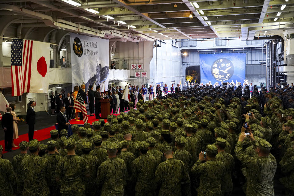 FILE - In this May 28, 2019, file photo, Japanese Prime Minister Shinzo Abe delivers a speech to Japanese and U.S. troops with U.S. President Donald Trump as they aboard Japan Maritime Self-Defense Force's (JMSDF) helicopter carrier DDH-184 Kaga at Yokosuka base in Yokosuka, south of Tokyo. Japan approved Friday, Dec. 20, 2019, a draft defense budget that included cost to develop own fighter jets to succeed the nation's aging warplanes and import some of F-35 stealth fighters as components for assembly at home rather than importing the expensive American warplanes as finished products to reduce costs and acquire expertise. Japan's defense spending has risen for seven consecutive years by a total of 13%, beginning a year after Abe took office in December 2012. (Athit Perawongmetha/Pool Photo via AP, File)
