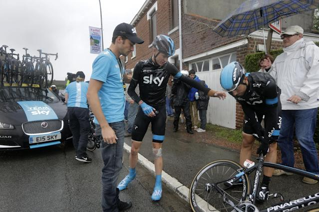 Britain's Christopher Froome gestures to his teammate Spain's Xabier Zandio, right, as he gets up after a third consecutive crash in two days prior to abandoning the race during the fifth stage of the Tour de France cycling race over 155 kilometers (96.3 miles) with start in Ypres, Belgium, and finish in Arenberg, France, Wednesday, July 9, 2014. The stage initially contained nine sectors of cobblestone roads dreaded by the majority of the riders in the pack especially under wet conditions, the organization decided to cancel two of the nine stretches because of the weather. (AP Photo/Laurent Cipriani)