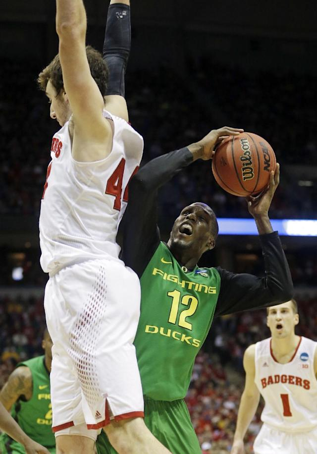 Oregon guard Jason Calliste (12) drives to the basket against Wisconsin forward Frank Kaminsky (44) during the first half of a third-round game of the NCAA college basketball tournament Saturday, March 22, 2014, in Milwaukee. (AP Photo/Morry Gash)