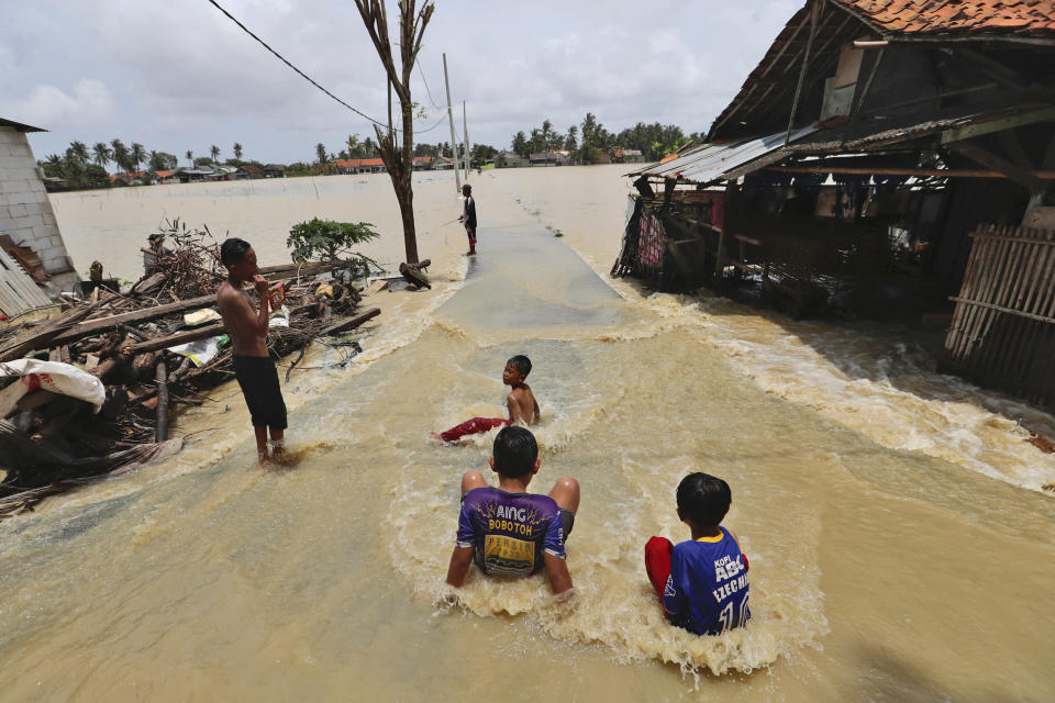 Children play in the water at a neighborhood flooded after the Citarum River embankment in Bekasi, Indonesia, Monday, Feb. 22, 2021. Thousands of residents are affected and being evacuated as some areas in Bekasi. (AP Photo/Achmad Ibrahim)